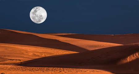 noche y luna: Gran luna llena que se levanta sobre las dunas de arena de color naranja