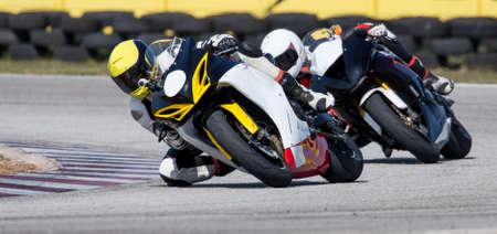 casco moto: Dos motocicletas de carreras en una curva cerrada
