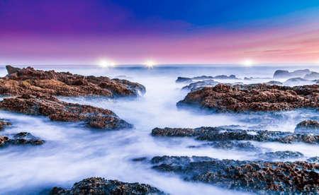 海の波と南アフリカ共和国の海岸の岩の長時間露光