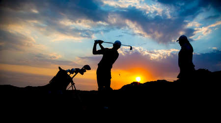 Silhouette of a golf couple playing golf at sunset