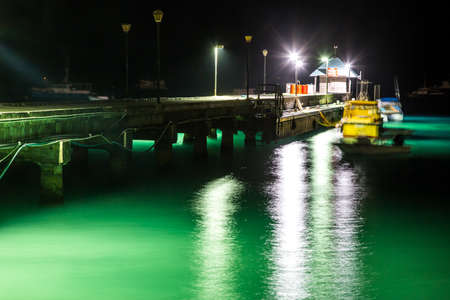 A fishing jetty and clear water in Barbados lit up and night