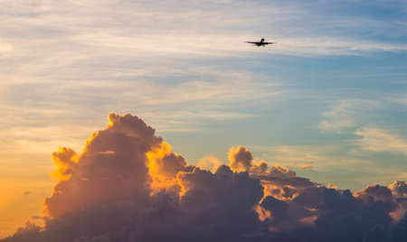 Passenger Jet Aeroplane high above the clouds at sunset