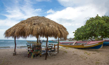 Typical Jamaican beach shelter and fishing boats on the beach at Treasure Beach