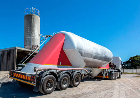 Large cement delivery truck with cement silo in the background Reklamní fotografie