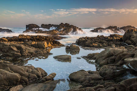 Rocky shoreline with tidal pools and waves Reklamní fotografie
