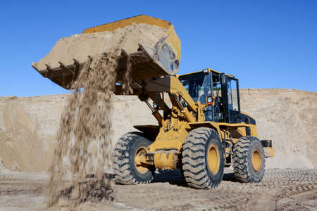 A front end loader machine tipping sand in a quarry
