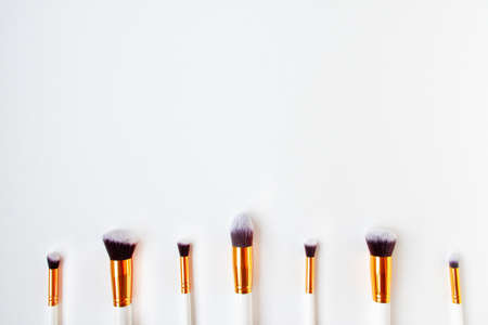 Flat lay top view of female cosmetics brushes set for makeup, are located at the bottom on white background. Cosmetics and beauty concept. Make up concept with space for text