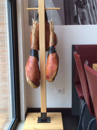 daniele: The finest prosciutto hangs in an Italian restaurant ready to be used. Stock Photo