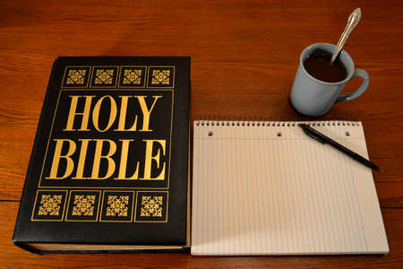 Bible, notebook & coffee on table (place for text on notebook) photo