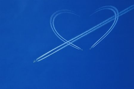 Blue sky with white jet and heart photo