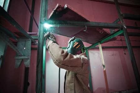 welder in protective mask welding metal construction inside Stock Photo
