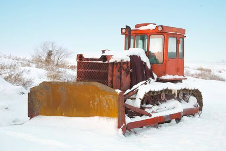The heavy building bulldozer of yellow color on snow winter photo