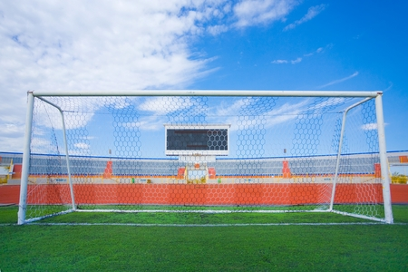Football field with goal and tablo on blue sky
