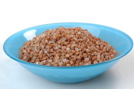 groats porridge in plate on white