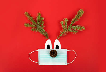 Christmas parties during the Covid-19 pandemic. surgical mask with fir branches representing a deer. Banque d'images
