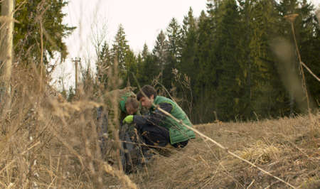 Young couple eco volunteers collecting garbage on the road near the forest in spring. Green conifers trees, last years dry grass. Earth day, eco friendly concept