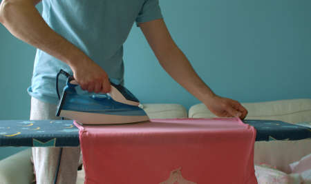 Close up hands of young handsome man ironing clothes. He irons his wifes t-shirt. Clean but not ironed clothes are lying on a sofa. Domestic daily life. Household man 版權商用圖片