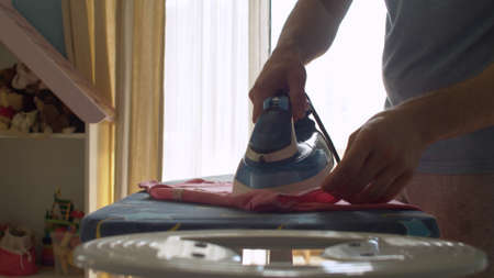 Close up hands of young handsome man ironing clothes. He irons his wifes t-shirt. Domestic daily life. Household man 版權商用圖片