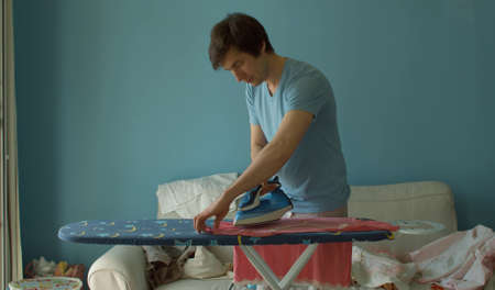 Young handsome man ironing clothes. He irons his wifes t-shirt. Clean but not ironed clothes are lying on a sofa. Domestic daily life. Household man