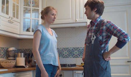 Plumber in overalls and young housewife in the kitchen. They are discussing something. Plumbing in need of repair.