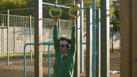 Funny freak man in green hoodie, color shorts and sunglasses pulling up on the rings on the sportground outdoors. Sport humor concept.
