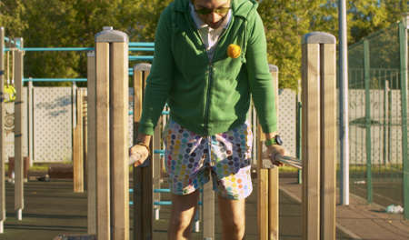 Funny freak man in green hoodie, color shorts and sunglasses pushing up on parallel bars on the sportground outdoors. Sport humor concept. Archivio Fotografico