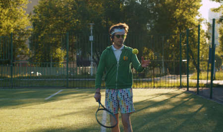 Funny freak man with tennis racket in his hand playing tennis ball on the sportground in the park. Sport humor concept.