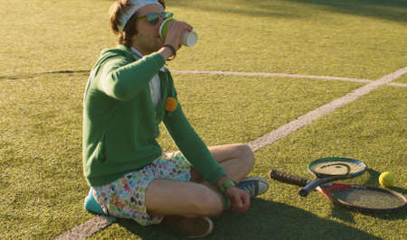Funny freak man sitting on the tennis court and drinking hot drink. Rest after playing sports outdoors. Sport humor concept. Archivio Fotografico