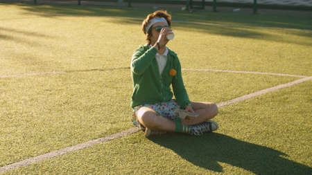 Funny freak man sitting on the tennis court and drinking tea. Rest after playing sports outdoors. Sport humor concept.