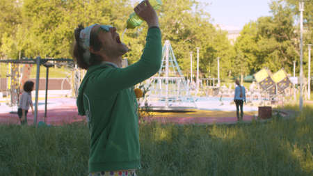 Funny freak man in the park drinking water. He sprays water in his mouth from a bottle. Rest after sports training outdoors. Sport humor concept.