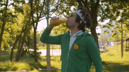 Funny freak man in the park drinking juice. Rest after sports training outdoors. Sport humor concept.