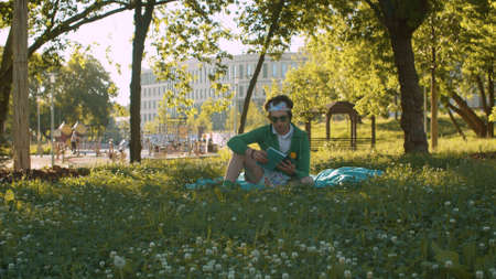 Funny freak man green hoodie, color shorts and sunglasses sitting on the grass in the park and reading a book. Humorous leisure concept Archivio Fotografico