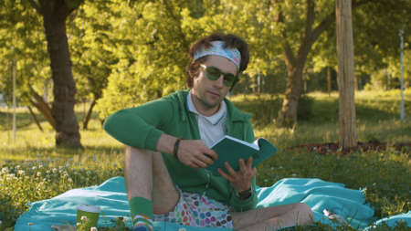 Humorous portrait of a funny freak man sitting on the grass in the park and reading a book. Humorous leisure concept