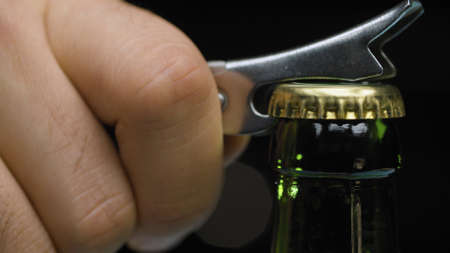 Macro shot male hand opening bottle of beer using opener on black background