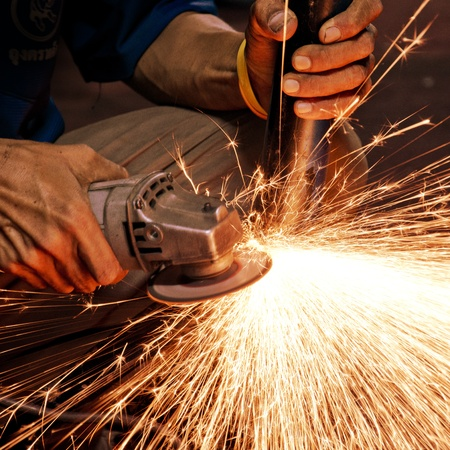 steel making: Worker making sparks while welding steel  Stock Photo