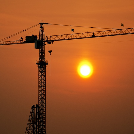 Industrial construction cranes and building silhouettes with sunrise Stock Photo - 13055776