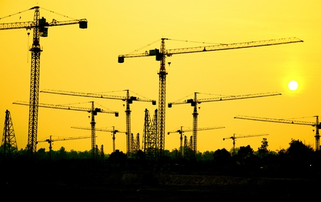 Industrial construction cranes and building silhouettes with sunrise