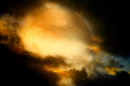 A dark night brings a bright, amber moon alive with puffy hazy clouds. photo