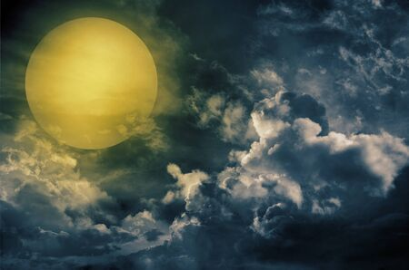 amber light: A dark night brings a bright, amber moon alive with puffy hazy