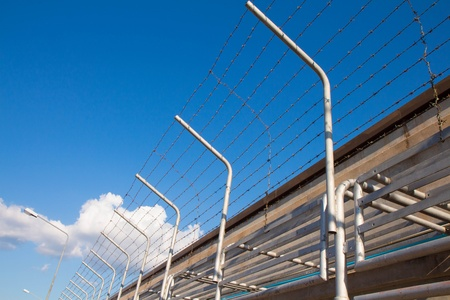 Barbed wire fence against the blue sky photo