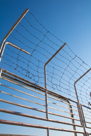 barbwire: Barbed wire fence against the blue sky Stock Photo