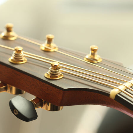 differential focus: Close up of tuning peg on acoustic guitar headstock Stock Photo