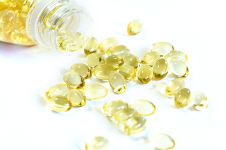 fish oil: Omega 3 fish oil capsules out open container on white background Stock Photo