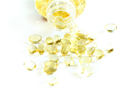 Omega 3 fish oil capsules out open container on white background photo