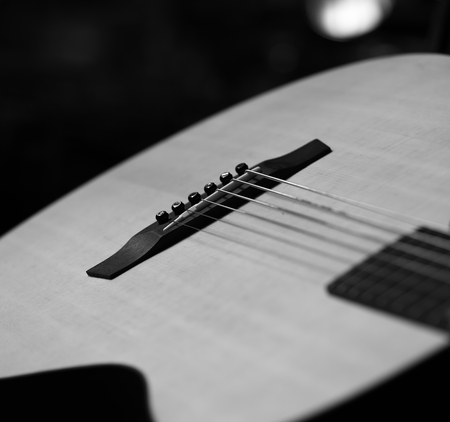 frets: Acoustic Guitar with very shallow depth of field, focus on strings. Black & White Stock Photo