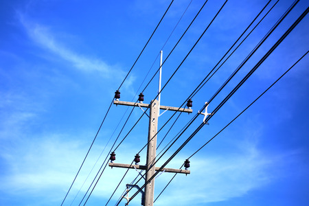 Electrical post with power line cables against blue sky photo