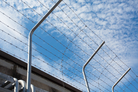 prison fence: Barbed wire fence against the blue sky Stock Photo