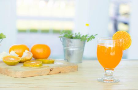sweet segments: Orange juice in glass , fresh fruits on wooden background