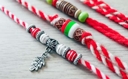 Bulgarian traditional spring decor martenitsa bracelets, wooden background. Baba Marta holiday, backdrop.