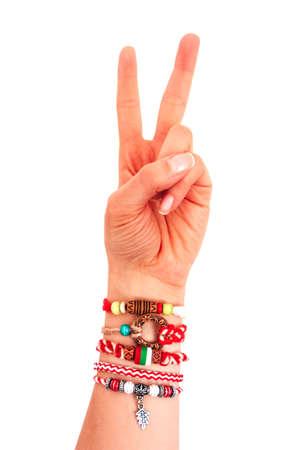 Bulgarian traditional spring decor bracelet martenitsa, female hand two fingers. Baba Marta holiday, peace gesture, isolated on white background.